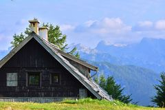 Wooden house high in the mountains. With green grass in the foreground and with mountains and sky for the background royalty free stock images