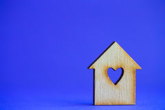 Wooden house with hole in form of heart on blue background Royalty Free Stock Photos
