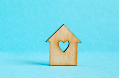 Wooden house with hole in the form of heart on blue background. Horizontal Stock Images