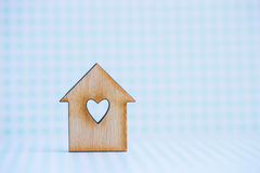Wooden house with hole in form of heart on blue checkered backgr. Ound Stock Image