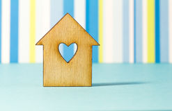 Wooden house with hole in the form of heart on blue striped back Stock Photography
