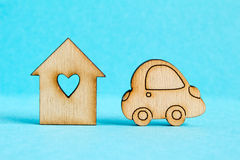 Wooden house with hole in the form of heart with car icon on blu Royalty Free Stock Photos