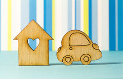 Wooden house with hole in the form of heart with car icon on blu Royalty Free Stock Image