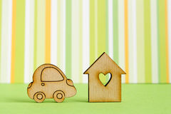 Wooden house with hole in the form of heart with car icon on green striped background royalty free stock photo
