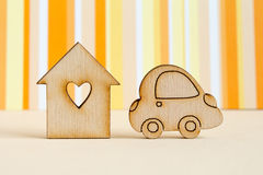 Wooden house with hole in the form of heart with car icon on ora. Nge striped background Stock Image