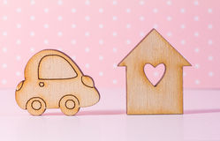 Wooden house with hole in the form of heart with car icon on pin Royalty Free Stock Image