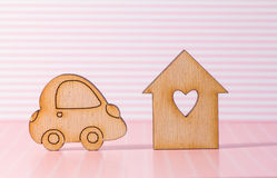 Wooden house with hole in the form of heart with car icon on pin Stock Photo