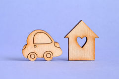 Wooden house with hole in the form of heart with car icon on purple background.  royalty free stock photography