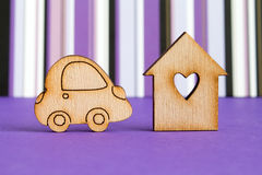 Wooden house with hole in the form of heart with car icon on purple striped background.  royalty free stock photography