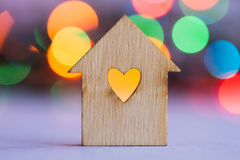 Wooden house with hole in the form of heart on colorful bokeh ba Stock Image
