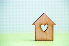 Wooden house with hole in form of heart on green checkered backg. Round Stock Image