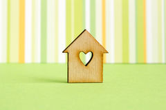 Wooden house with hole in the form of heart on green striped bac. Kground horizontal Stock Images