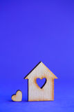 Wooden house with hole in form of heart with little heart on blu Stock Image