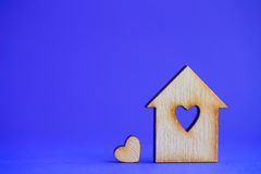 Wooden house with hole in form of heart with little heart on blu Royalty Free Stock Photos