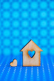 Wooden house with hole in form of heart with little heart on blu Royalty Free Stock Photo