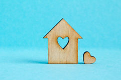 Wooden house with hole in the form of heart with little heart on. Blue background horizontal Royalty Free Stock Images