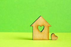 Wooden house with hole in the form of heart with little heart on. Green background horizontal Royalty Free Stock Image