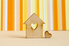 Wooden house with hole in the form of heart with little heart on. Orange striped background horizontal Royalty Free Stock Images