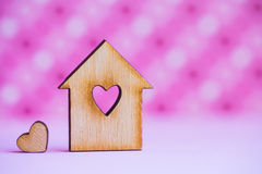 Wooden house with hole in form of heart with little heart on pin Royalty Free Stock Photography