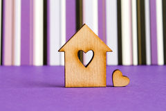 Wooden house with hole in the form of heart with little heart on. Purple striped background horizontal Stock Photos