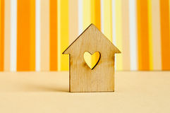 Wooden house with hole in the form of heart on orange striped ba. Ckground horizontal Stock Photos