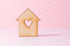 Wooden house with hole in the form of heart on pink background Stock Photos