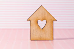 Wooden house with hole in the form of heart on pink striped back Stock Photography