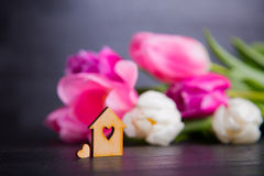 Wooden house with hole in form of heart with pink tulips Royalty Free Stock Photos