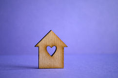 Wooden house with a hole in the form of heart on a purple backgr. Ound Royalty Free Stock Image