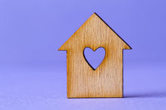 Wooden house with hole in the form of heart on purple background. Wooden house with a hole in the form of heart on a purple background horizontal Stock Photos