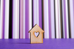 Wooden house with hole in the form of heart on purple striped ba Royalty Free Stock Photos