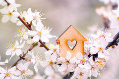 Wooden house with hole in form of heart surrounded by flowering Royalty Free Stock Images