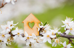 Wooden house with hole in form of heart surrounded by flowering Stock Image