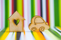 Wooden house with hole in form of heart with wooden car icon on. Colorful striped background. Concept of moving. Symbol of traveling stock photos