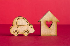 Wooden house with hole in the form of heart with wooden car icon. On red background Stock Photos