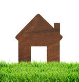 Wooden house icon on green grass isolated on white background Royalty Free Stock Photo