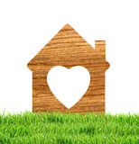 Wooden house icon in green grass  on white Stock Image