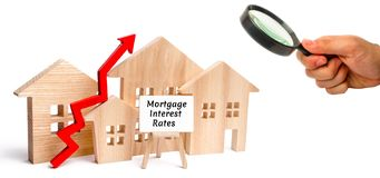 Wooden house and the inscription Mortgage interest rates and up arrow. Raising mortgage rates and tax. The increase in interest. Charges. Reduced demand for stock photography