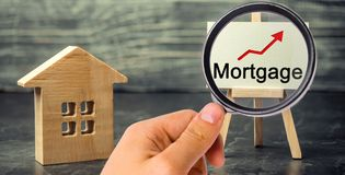 Wooden house and the inscription Mortgage and up arrow. Raising mortgage rates and tax. The increase in interest charges. Reduced stock photo