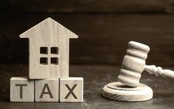 Wooden house with the inscription `Tax` and the judge`s hammer. Taxes on real estate, payment. Penalty, arrears. Register of taxpa. Yers for property. Law stock images