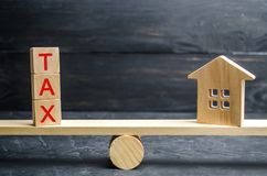 Wooden house with the inscription `Tax` on the scales. Taxes on real estate, payment. Penalty, arrears. Register of taxpayers for stock photo