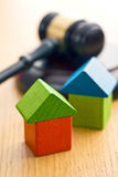Wooden house and judge gavel. The wooden house and judge gavel on wooden table Stock Photos