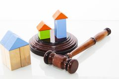 Wooden house and judge gavel on a white background. Is isolated. stock image