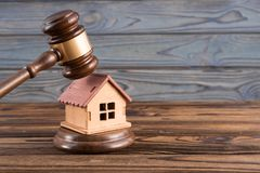 Wooden house, judge`s gavel on wooden background. stock images