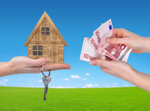 Wooden house with key and Euro money in hands Stock Photography