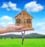 Wooden house with key in hand Stock Photography
