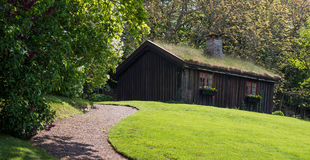 A wooden house on a landscaped lawn under with a path Stock Images