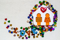 Wooden house with little man and bright confetti heart-shaped Royalty Free Stock Images