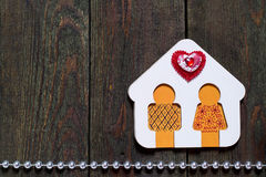 Wooden house with little man and heart. Symbol of love and fidelity - hand-painted wooden house with little man and hearts on old wooden surface with space for Stock Images