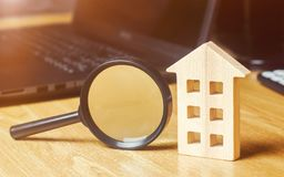 Wooden house and magnifying glass. Property valuation. Choice of location for the construction. House searching concept. Search. For housing and apartments royalty free stock image